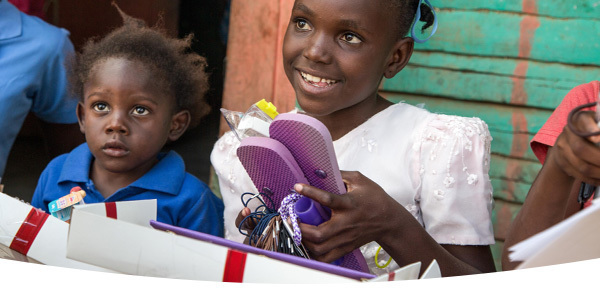 Beneficiary girl smiling and holding her Box of Joy.